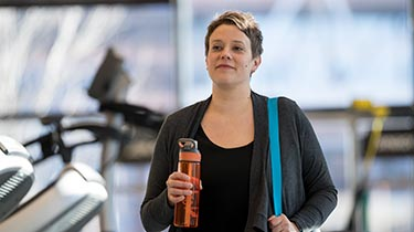 Woman drinking out of water bottle while walking through gym